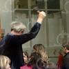 """W031<br /> Intussen is de handbel aan Wim overgegeven. Bij de hoofdingang """"belt"""" hij bij het begin van de schooltijd de kinderen """"naar binnen"""". We gaan dus niet meer in rijen naar binnen. Wim kent vrijwel alle (± 350) kinderen bij naam."""