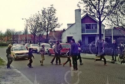 W020<br /> Sjanie Habers en Gerard Knoef zorgen dat de kinderen veilig oversteken vanaf het speelveld achter de school. Sjanie hanteert de handbel – die is van verre te horen. In de verte huizen aan de Charbonlaan.