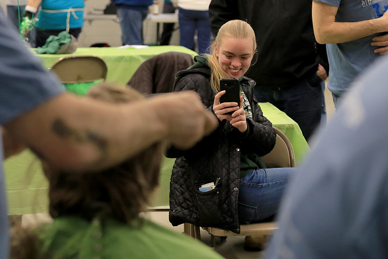 The annual St. Baldrick's event has held at the Pepperell Fire Department on Park Street on Wednesday night in Pepperell. Participants donate money to get people to cut their hair short to raise money for childhood cancer research. Emma King of Townsend watched and took pictures of her brother Daniel King as he got his hair cut at the event. SENTINEL & ENTERPRISE/JOHN LOVE