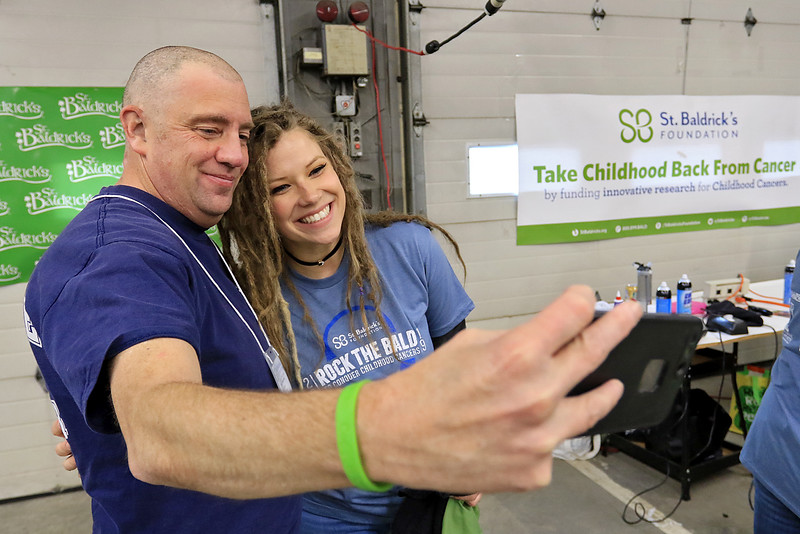The annual St. Baldrick's event has held at the Pepperell Fire Department on Park Street on Wednesday night in Pepperell. Participants donate money to get people to cut their hair short to raise money for childhood cancer research. After getting his hair cut Brad Biscornet takes a picture with Tarah Nooman who was one of the volunteeers that cut his hair. SENTINEL & ENTERPRISE/JOHN LOVE