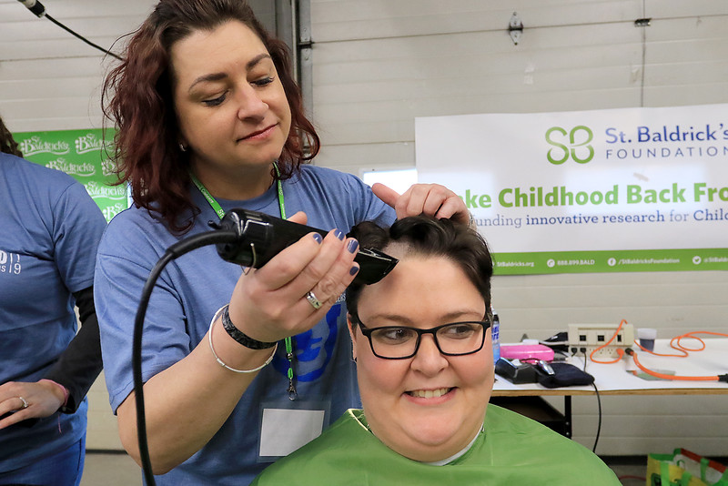 The annual St. Baldrick's event has held at the Pepperell Fire Department on Park Street on Wednesday night in Pepperell. Participants donate money to get people to cut their hair short to raise money for childhood cancer research. Participant Gina Sennott of Pepperell gets her hair cut by Christina Ziegler with Serenity Spa and Salon in Tyngsboro at the event. SENTINEL & ENTERPRISE/JOHN LOVE
