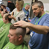 The annual St. Baldrick's event has held at the Pepperell Fire Department on Park Street on Wednesday night in Pepperell. Participants donate money to get people to cut their hair short to raise money for childhood cancer research. On the end is participant Josh Abbott, a Chelmsford firefighter, getting his hair cut by Joe Lisio of Patriot Barber Shop in Pepperell. SENTINEL & ENTERPRISE/JOHN LOVE