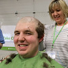 The annual St. Baldrick's event has held at the Pepperell Fire Department on Park Street on Wednesday night in Pepperell. Participants donate money to get people to cut their hair short to raise money for childhood cancer research. Participant Tom Geoffroy, a Tyngsboro firefighter, gets his hair cut by Kyle Belair of Patriot Barber Shop in Pepperell. SENTINEL & ENTERPRISE/JOHN LOVE