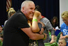 HOLLY PELCZYNSKI - BENNINGTON BANNER Father and son Kirk Moore and 4th grader Grayson Moore embrace in a hug after both getting thier heads shaved during The St. Baldrick's foundation on Wednesday morning at Manchester Elementary school.