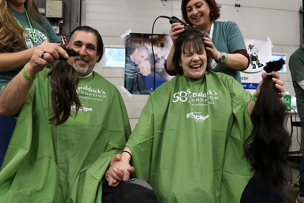 . The 16th annual St. Baldrick\'s fundraiser was held by the Pepperell Fire Department on Wednesday night, March 14, 2018. Nicole Sweeney, who works for the Pepperell Fire Department, and her husband Charlie Sweeney show off their ponytails that had just gotten cut off as they participated in the event. SENTINEL & ENTERPRISE/JOHN LOVE