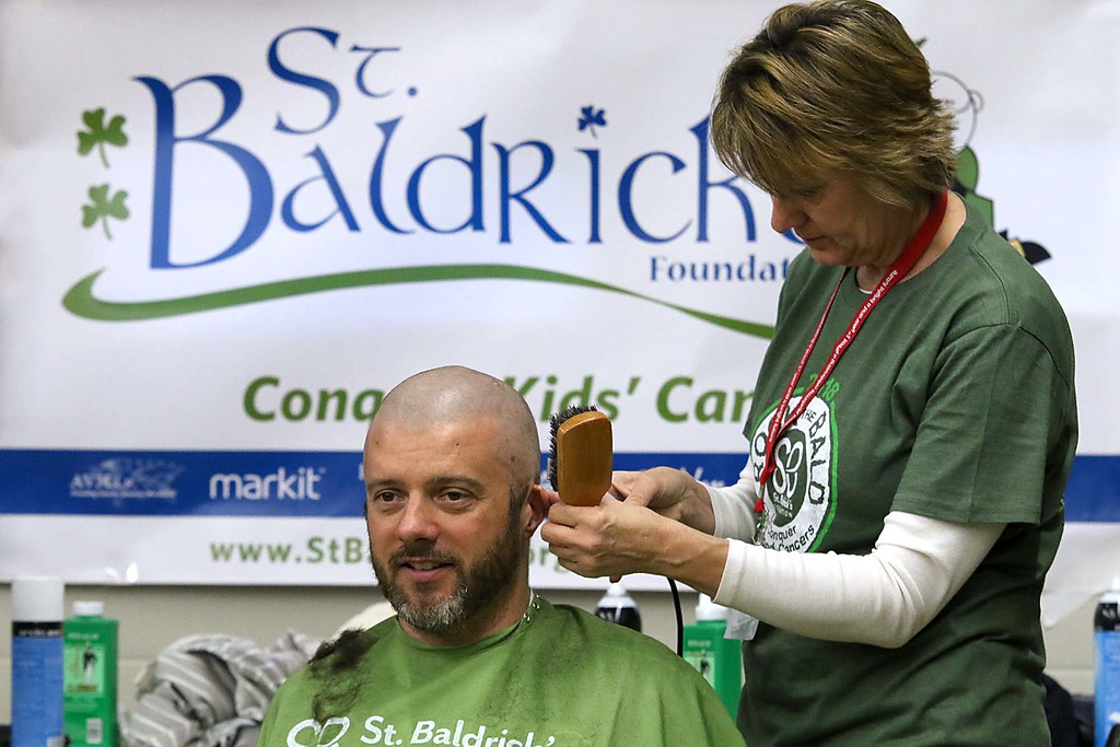 . The 16th annual St. Baldrick\'s fundraiser was held by the Pepperell Fire Department on Wednesday night, March 14, 2018. B.J. Swygart of Westford gets his hair cut by Kyle Belair from Patriots Barbershop in Pepperell at the event. SENTINEL & ENTERPRISE/JOHN LOVE