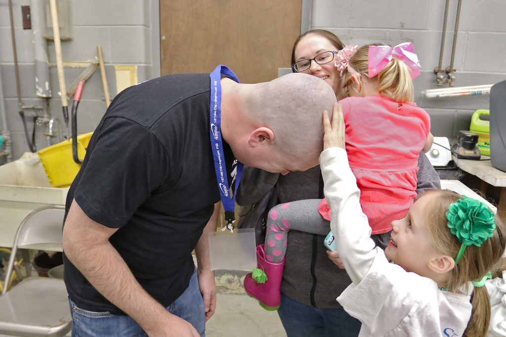 . The 16th annual St. Baldrick\'s fundraiser was held by the Pepperell Fire Department on Wednesday night, March 14, 2018. Tammy Abbot hold her girls Evelyn Abbott, 3, as  Lillian Abbott, 6, feels father her father Josh Abbott\'s, a Chelmsford firefighter, head after he got all his hair cut off for the cause. SENTINEL & ENTERPRISE/JOHN LOVE
