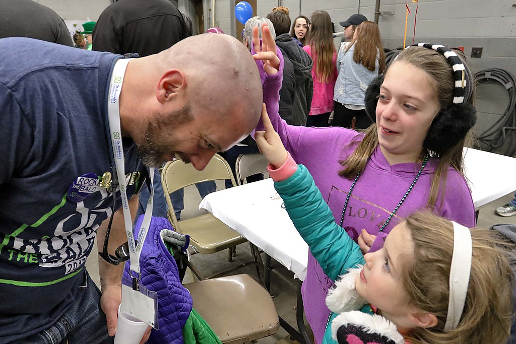 . The 16th annual St. Baldrick\'s fundraiser was held by the Pepperell Fire Department on Wednesday night, March 14, 2018. Colette Swygart, 5, and Ava Swagart, 9, of Westford fweel their dad\'s ,B.J. Swygart, head after he got his hair cut for the cause. SENTINEL & ENTERPRISE/JOHN LOVE
