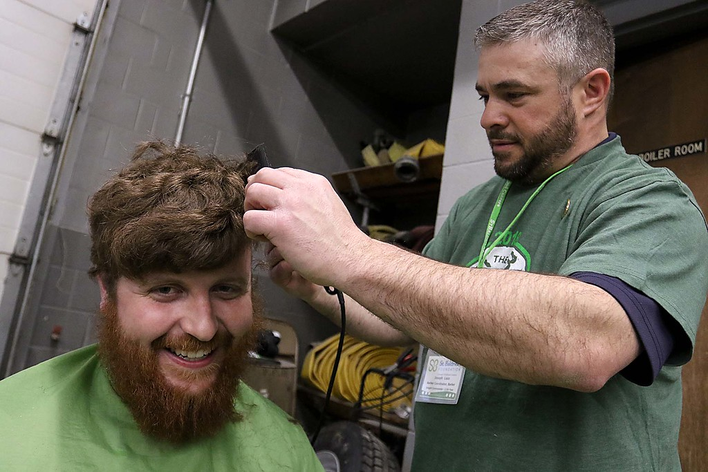 . The 16th annual St. Baldrick\'s fundraiser was held by the Pepperell Fire Department on Wednesday night, March 14, 2018. Participant Tom Bradley of Lunenburg gets his hair cut by Joe Lisio from Patriots Barbershop in Pepperell. SENTINEL & ENTERPRISE/JOHN LOVE