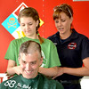 Nicole Lee shaves her father's head, Effingham Fire Lieutenant Jason Lee.