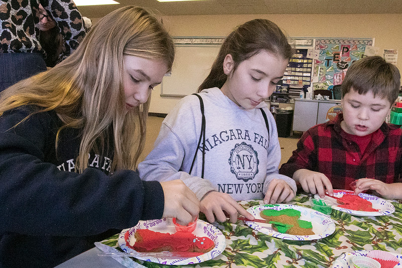 St. Bernard's Elementary School's Holiday Fair Saturday, Nov. 23, 2019. Decorating cookies at the fair is, from left, Twins Anna and Ina Soini, 11, and their brother Aleksey Soini, 5, all from Fitchburg. SENTINEL & ENTERPRISE/JOHN LOVE