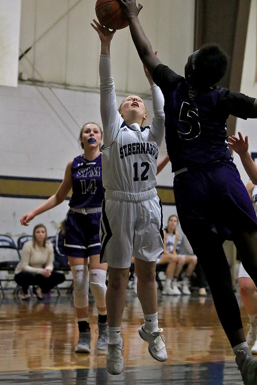 . St. Peter-Marian High School girls basketball played St. Bernard�s High School in Fitchburg on Thursday afternoon. St. B\'s Hadleigh Bigelow gets her shoot blocked by St. Peter-Marian\'s Faith Greene during action in the game. SENTINEL & ENTERPRISE/JOHN LOVE