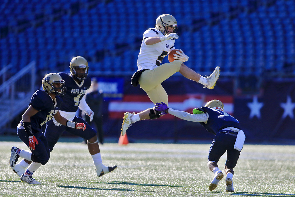 . St. Bernard�s played Pope John XXIII at Gillette Stadium in Foxborough on Saturday morning, December 1, 2018 for the Division 8 state final game. St. B\'s Xavier Marty leaps over Pope John\'s John Smith Howell to get some more yards. SENTINEL & ENTERPRISE/JOHN LOVE