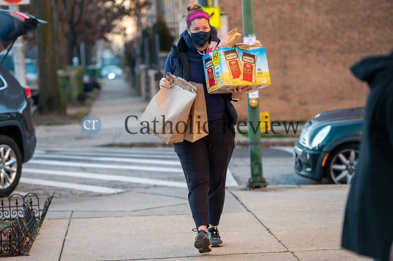 Beth Malafk, a parishioner at Sacred Heart of Jesus- Sagrado Corazón de Jesús in Highlandtown, drops off lunches prepared for the St. Casimir Catholic Church, Canton, outreach supporting the St. Vincent de Paul Beans and Bread Center on S. Bond St. (Kevin J. Parks/CR Staff)