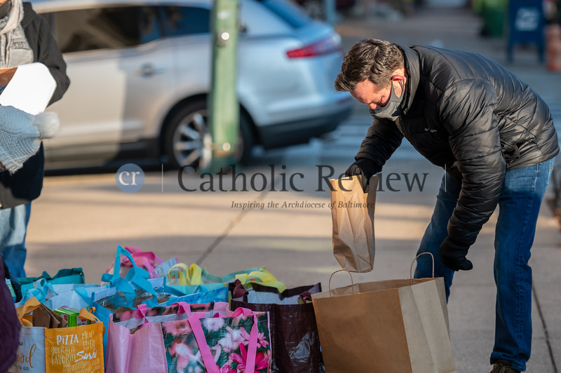 Chuck Lee, a parishioner at St. Casimir Catholic Church in Canton, prepares for delivery a portion of the 1,100 lunches prepared by parish volunteers and local residents Jan. 12 for delivery to the St. Vincent de Paul Bean and Bread Center on S. Bond St. (Kevin J. Parks/CR Staff)