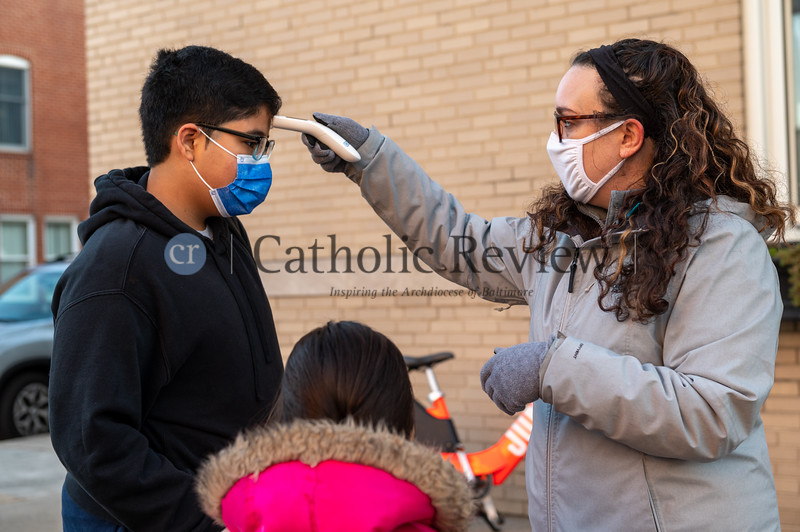 Bekky Buckmeier, nurse at St. Casimir Catholic School in Canton, performs temperature checks Jan. 12 before students enter the building for class.(Kevin J. Parks/CR Staff)