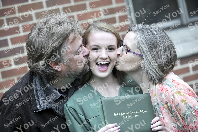 -Messenger photo by Hans Madsen<br /> <br /> Ayrton Peterson reacts as she gets a double kiss from her parents, Neil and Tina Peterson, following commencement at St. Edmond Catholic School.