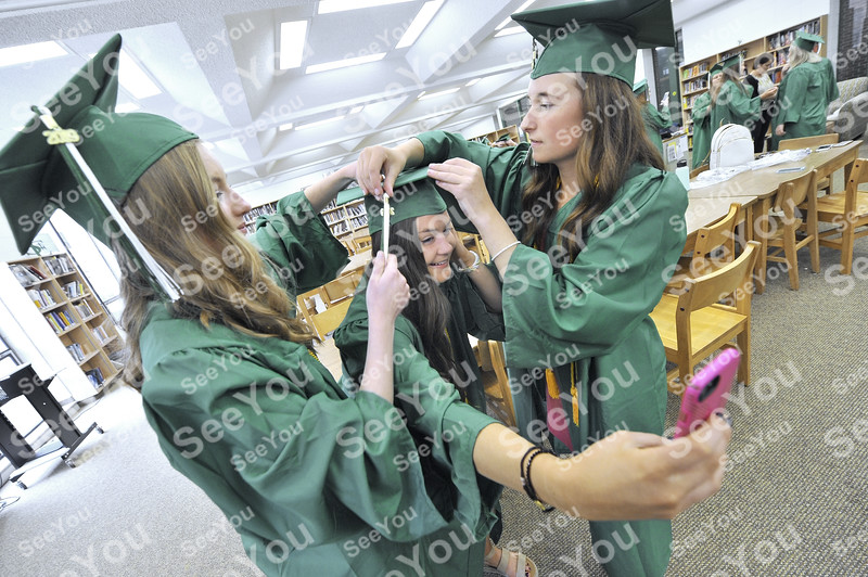 -Messenger photo by Hans Madsen<br /> <br /> Erin Flattery, center, takes a selfie as she gets help with getting her cap on Sunday afternoon from her classmates Jillian Cosgrove, at left, and Jacquelynn Oberg, right.