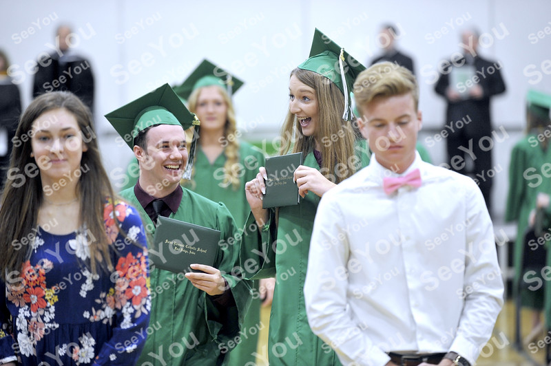 -Messenger photo by Hans Madsen<br /> <br /> Carlee Rautanen, right, is all smiles as she holds up her diploma for a family member in the audience as the St. Edmond Catholic School Class of 2019 leaves the auditorium after commencement. At left, Jake Rossow is all smiles too.