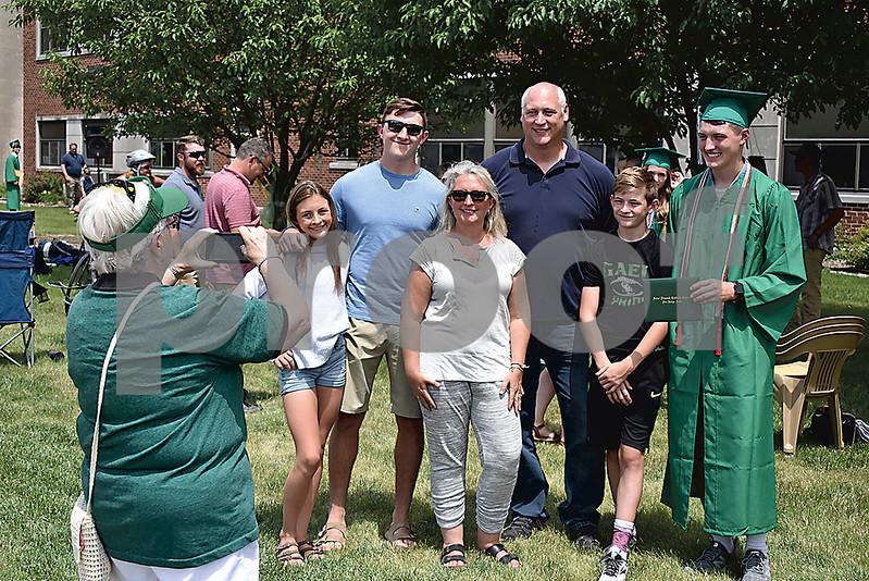 -Messenger photo by Elijah Decious<br /> <br /> St. Edmond graduate Ethan Lursen, right, takes family photos after commencement Sunday.