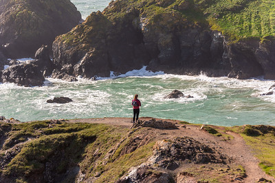 A young woman stares out across the rough seas at Kynance COve, Cornwall, UK