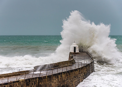 A massive wave hits Portreath Harbour Wall during Storm Dennis, Cornwall, UK