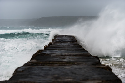 Waves crash against the harbour wall during Storm Dennis at Sennen Cove, Cornwall, UK