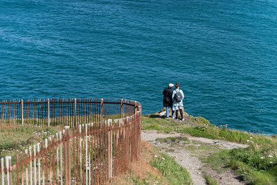 A young couple stand at the end of a cliff and look out across the sea at St Ives, Cornwall, UK