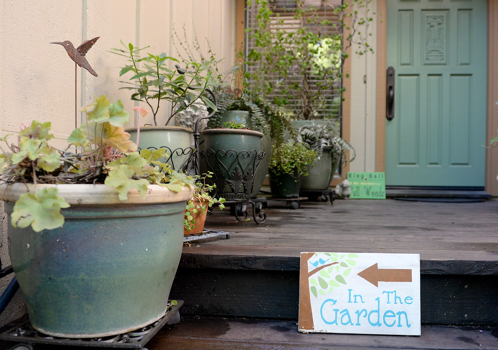 . A sign posted on the front porch area directs visitors to the garden during a tour of the garden at Ruth Guzley\'s residence in Chico, Calif. Friday April 14, 2017. This is one of the gardens that will be featured during the St. John Episcopal Church Garden Tour.  (Bill Husa -- Enterprise-Record)
