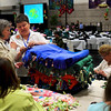 A member of the assembly is shown how to tie the top and bottom pieces of a fleece blanket together. Members of the ECSW made 409 blankets over the two days of the assembly. They will be given to some of the nearly 700 students in the Green Bay School district who are known to be homeless.