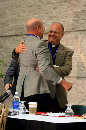 Bishop James A. Justman of the East Central Synod of Wisconsin is congratulated by synod VP John Emery upon his re-election to his third term on the first ballot.