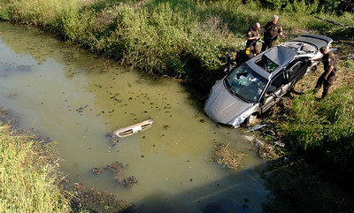 ELISA PETERSEN / Courier & Press Vanderburgh County Sheriff's Department deputies work at the scene of a vehicle that crashed into the water near Waterworks and Weinbach on Thursday afternoon, Sept. 13, 2007. The department said four passengers were found and transported to the hospital.