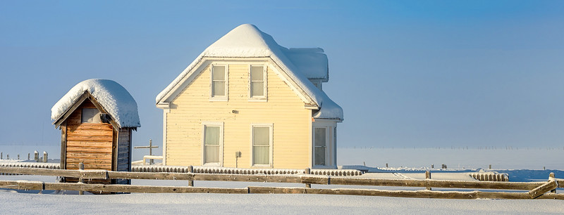 Winter farm house in Idaho with fence