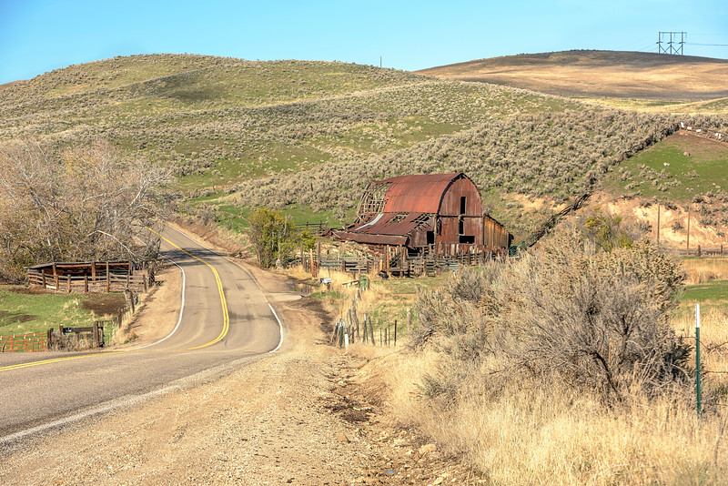 Country road leads past a rusted old barn