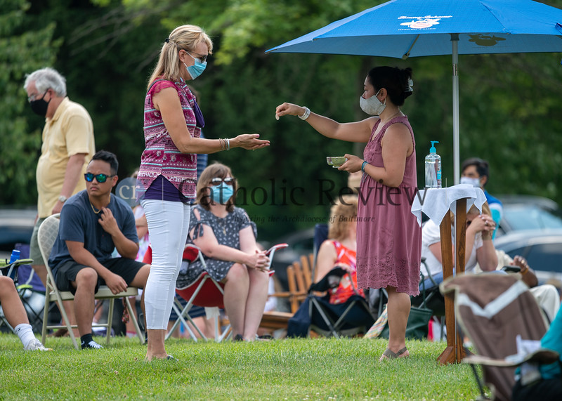 Gemma Armstrong distributes Communion from under an umbrella during the 11 am outdoor Mass June 28, 2020 on the grounds of St. Mary Magdalen Mission in Bel Air. Some 300 parishioners were in attendance. (Kevin J. Parks/CR Staff)