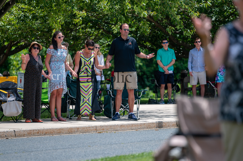 With a tree providing some shade, Jeanne Weaver, from left, Rachel Saaks, Sara Saaks and Nick Saaks pray the Our Father during the 11 am outdoor Mass June 28, 2020 on the grounds of St. Mary Magdalen Mission in Bel Air. (Kevin J. Parks/CR Staff)