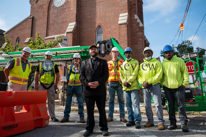 Father Joshua Laws, pastor of St. Mary, Star of the Sea in South Baltimore, stands with the crew from Lewis Contractors in Owings Mills following the reinstallation of the parish's steeple cross Oct. 20. (Kevin J. Parks/CR Staff)