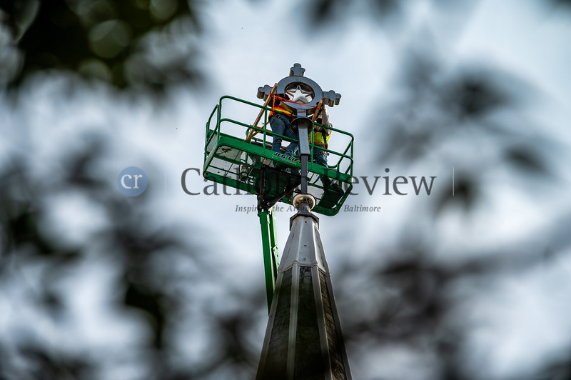 Crews from Lewis Contractors in Owings Mills gently slide into place the St. Mary, Star of the Sea Church steeple cross Oct. 20 in South Baltimore. Storms last spring left the neighborhood icon dangling requiring repairs.(Kevin J. Parks/CR Staff)