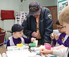 HOLLY PELCZYNSKI - BENNINGTON BANNER Elijah Abbott and William Wright kindergartners at St.  Mary's Academy paint Easter eggs with Veteran Marine Sailor Ed Taylor of Delmar NY on Tuesday morning at the Hoosick Falls Senior Center.