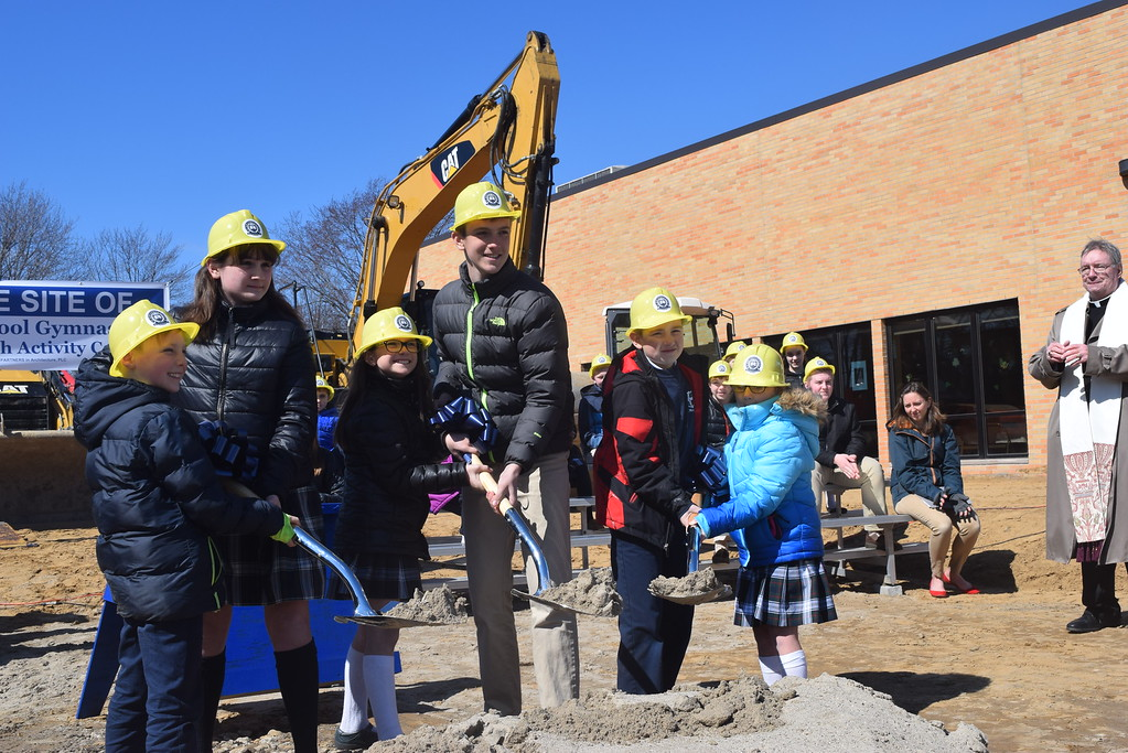 . Students from St. Mary\'s School raise their shovels during Friday\'s official ground-breaking for the new gymnasium being built at the school in Mount Clemens.