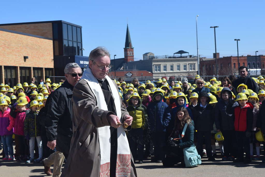 . Fr. Michael Clooney, pastor of St. Peter Parish and St. Mary Catholic School performs a blessing during Friday\'s ground-breaking ceremony for the school\'s new gymnasium. Gina Joseph - The Macomb Daily