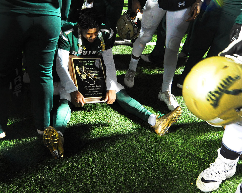 . MARTINEZ, CA- DEC. 2, St. Patrick-St. Vincent\'s Kailon Johnson-loud takes a moment to reflect as he sits on the ground in the middle of a crowd with the first place plaque after the Bruin\'s 28-0 win over Middletown in the North Coast Section title game on Saturday. (CHRIS RILEY/Times-Herald)