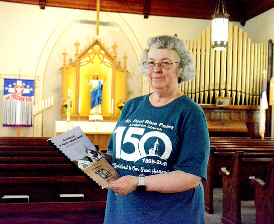 "Linda Schmidt, who has been a member of the congregation for 54 years, created a book about the 150 year history of the church entitled, ""The History of St. Paul Ev. Lutheran Church."" Schmidt provided the content for the book while Rachel Hammer created the layout and design. Charles Mills photo"