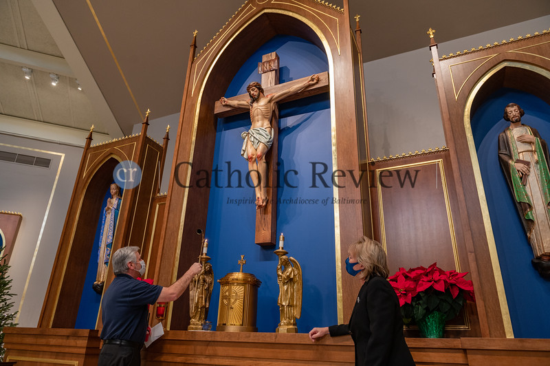 Mark Rachid, parish manager, right, and Diane Neighoff, sacristan, light candles in the new sanctuary at St. Philip Neri Church in Linthicum Heights following a six month, $1.5 million renovation. (Kevin J. Parks/CR Staff)