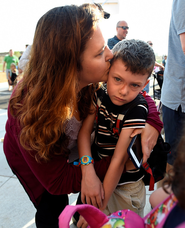 . BROOMFIELD, CO: August 15:  Emily Stanton, kisses her son, William, a first-grader, goodbye, during the first day of school at Thunder Vista P-8 in Broomfield on August 15, 2018. (Photo by Cliff Grassmick/Staff Photographer).