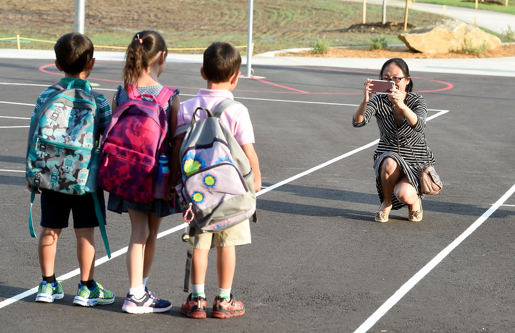 . BROOMFIELD, CO: August 15: Xiao LI takes a photo of her children, Kevin, April, and Tim Zhang, during the first day of school at Thunder Vista P-8 in Broomfield on August 15, 2018. (Photo by Cliff Grassmick/Staff Photographer).