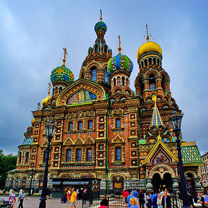 "The Church of the Savior on the Spilled Blood   (Russian: Храм Спаса на Крови) Khram Spasa na Krovi is one of the main sights of St. Petersburg, Russia. It is also variously called the Church on Spilt Blood and the Cathedral of the Resurrection of Christ (Russian: Собор Воскресения Христова), its official name. ""The preferred Russian name for this great church is [Храм Спаса на Крови] Khram Spasa na Krovi, but each English-language tourist publication seems to list it under a different name. The moniker of ""Spilled Blood"" is most popular in preference to the likes of the Church of the Resurrection, Church of our Savior on the Blood, Cathedral of the Ascension, Resurrection of the Christ, or Assumption, Church of the Redeemer, or any permutation of the above."" [1] This Church was built on the site where Tsar Alexander II was assassinated and was dedicated in his memory. It should not to be confused with the Church on Blood in Honour of All Saints Resplendent in the Russian Land, located in the city of Yekaterinburg where the former Emperor Nicholas II (1868-1918) and several members of his family and household were executed following the Bolshevik Revolution.  Construction began in 1883 under Alexander III, as a memorial to his father, Alexander II. Work progressed slowly and was finally completed during the reign of Nicholas II in 1907. Funding was provided by the Imperial family with the support of many private donors. The Church is prominently situated along the Griboedov Canal. The embankment at that point runs along either side of a canal. On March 13, 1881 (Julian date: March 1), as Tsar Alexander's carriage passed along the embankment, a grenade thrown by an anarchist conspirator exploded. The tsar, shaken but unhurt, got out of the carriage and started to remonstrate with the presumed culprit. Another conspirator took the chance to explode another bomb, killing himself and mortally wounding the tsar. The tsar, bleeding heavily, was taken back to the Winter Palace where he died a few hours later.   Detail of the richly decorated façade and onion domes A temporary shrine was erected on the site of the attack while the project for a more permanent memorial was undertaken. It was decided that the section of the street where the assassination took place was to be enclosed within the walls of a church. That section of the embankment was therefore extended out into the canal to allow the shrine to fit comfortably within the building and to provide space on the exterior wall for a memorial marking the spot where the assassination took place. Inside, an elaborate shrine was constructed on the exact place of Alexander's death, garnished with topaz, lazurite and other semi-precious stones. Amid such rich decoration, the simple cobblestones on which the tsar's blood was spilled and which are exposed in the floor of the shrine provide a striking contrast.  Source:  Wikipedia"