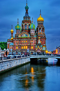"""Twilight photo of Church of the Savior on the Spilled Blood  Photo taken with a Nikon D3s and 24-120mm lens, set at 44mm.  Exposure:   ISO-200, f/11 @ 4 sec on a Benro carbon fiber tripod.  The Church of the Savior on the Spilled Blood   (Russian: Храм Спаса на Крови) Khram Spasa na Krovi is one of the main sights of St. Petersburg, Russia. It is also variously called the Church on Spilt Blood and the Cathedral of the Resurrection of Christ (Russian: Собор Воскресения Христова), its official name. """"The preferred Russian name for this great church is [Храм Спаса на Крови] Khram Spasa na Krovi, but each English-language tourist publication seems to list it under a different name. The moniker of """"Spilled Blood"""" is most popular in preference to the likes of the Church of the Resurrection, Church of our Savior on the Blood, Cathedral of the Ascension, Resurrection of the Christ, or Assumption, Church of the Redeemer, or any permutation of the above."""" [1] This Church was built on the site where Tsar Alexander II was assassinated and was dedicated in his memory. It should not to be confused with the Church on Blood in Honour of All Saints Resplendent in the Russian Land, located in the city of Yekaterinburg where the former Emperor Nicholas II (1868-1918) and several members of his family and household were executed following the Bolshevik Revolution.  Construction began in 1883 under Alexander III, as a memorial to his father, Alexander II. Work progressed slowly and was finally completed during the reign of Nicholas II in 1907. Funding was provided by the Imperial family with the support of many private donors. The Church is prominently situated along the Griboedov Canal. The embankment at that point runs along either side of a canal. On March 13, 1881 (Julian date: March 1), as Tsar Alexander's carriage passed along the embankment, a grenade thrown by an anarchist conspirator exploded. The tsar, shaken but unhurt, got out of the carriage and started to remonstrate with """