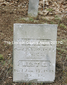 The headstone which marks the burials of Mark J. and West C. Sidelinger shows the signs of several attempts to repair it.