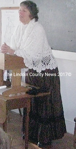 Carolyn Hardman (standing with shawl) is a NHS volunteer. She taught lessons in the one room schoolhouse to Nobleboro Central School sixth grade students on Wednesday. (J Maguire photo)